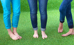 Three women with naked feet standing in grass Royalty Free Stock Photography