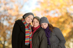 Three women outdoors in fall. Three women snuggled together in front of golden autumn foliage, copyspace Stock Images