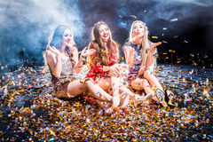 Three women at the party. Three stylish young women sitting on the floor covered with confetti Stock Photos