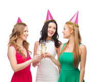 Three women in pink hats with champagne glasses Stock Images
