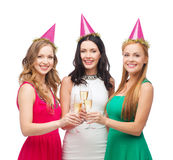 Three women in pink hats with champagne glasses Stock Photography