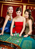 Three women place a bet playing roulette Royalty Free Stock Images