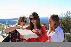 Women planning on vacation. Three female tourists planning the next move with the help of a map while standing on a visitor platform, Blue Mountains, Australia Royalty Free Stock Images
