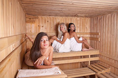 Three women relaxing a hot sauna Stock Photography