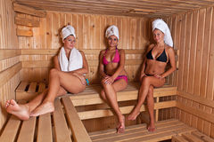Three women relaxing a hot sauna Stock Photos