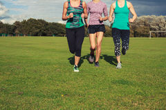 Three women running in the park Royalty Free Stock Photos