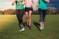 Three women running in the park stock image