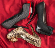 Three  women's beautiful  shoes lying on red silk Royalty Free Stock Photography