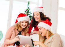Three women in santa helper hats with tablet pc Stock Photography