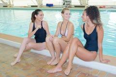 Three women sat on side pool Stock Photo
