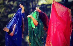 Three women during a sensual dance with long colorful clothes Stock Photos