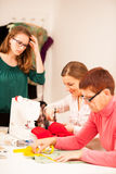 Three women are sewing on handcraft workshop. They are teaching Stock Image