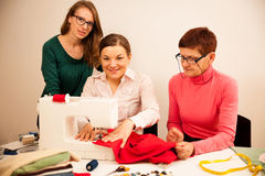 Three women are sewing on handcraft workshop. They are teaching Stock Photography