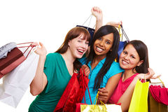 Three women with shopping bags. Three happy young women with many colorful shopping bags stock photography