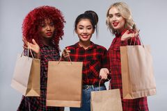Three women at shopping on Black Friday holiday. Beautiful young women make shopping in black friday holiday. Girls with bag on lgiht background Stock Image