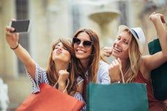 Three women shopping together and make selfie photo. Having fun royalty free stock photos