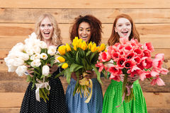 Three women showing bouquets of flowers at camera Royalty Free Stock Photos