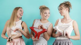 Three women showing high heels shoes. Three gorgeous women fashion stylist presenting stylish shoes. Sensual high heels presentation. Outfit accessories and Stock Photography