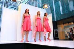 Three women showing pink dresses on the catwalk Stock Image