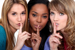 Three women shushing. Three women with the fingers to their lips Royalty Free Stock Photo