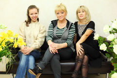 Three women sit on black leather couch stock photo
