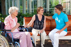 Three women sitting chatting on a garden bench. Three women sitting chatting on a garden bench with one old lady sitting in a wheelchair, while one elderly royalty free stock photography