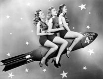 Three women sitting on a rocket. (All persons depicted are no longer living and no estate exists. Supplier grants that there will be no model release issues stock photography