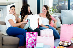 Three women sitting on sofa and looking at babys clothes stock photos