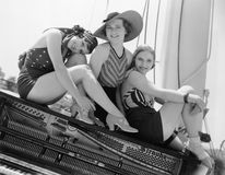 Three women sitting on top of a piano Royalty Free Stock Images