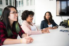 Three Women Sitting Beside White Table stock photography
