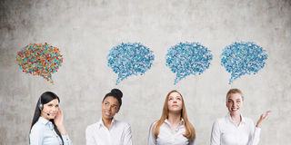 Three women speaking one language and a foreigner. Group of four women standing near concrete wall. They are speaking but only three of them understand each Royalty Free Stock Photos