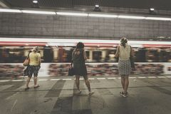 Three Women Standing in the Side of Running Train Royalty Free Stock Photo
