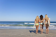 Three Women Surfers In Bikinis Surfboards Beach. Rear view of three Beautiful young women surfer girls in bikinis with white surfboards at a beach Royalty Free Stock Images