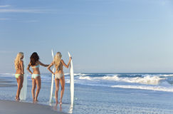 Three Women Surfers With Surfboards At Beach. Rear view of three Beautiful young women surfer girls in bikinis with white surfboards at a beach Royalty Free Stock Images