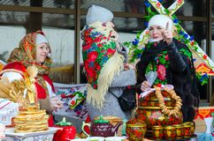 Three women are at table with pancakes and painted utensils during Shrovetide festivities. GOMEL, BELARUS - FEBRUARY 18, 2018: Three women are at table with Royalty Free Stock Images