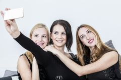 Three women take a selfie shot with their mobile phone royalty free stock photos