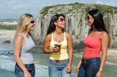 Three women taking chimarrão on Torres beach stock photography
