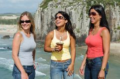 Three women taking chimarrão on Torres beach stock image