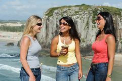 Three women taking chimarrão on Torres beach stock images