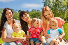 Three women with their babies sit on green grass Stock Photos