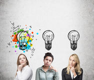 Three women thinking near concrete wall. Three women are standing near concrete wall and thinking. Light bulb images are drawn above their heads. One is colorful Stock Photos