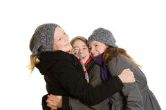 Three women in tight embrace. Laughing mother an her daughters in winter clothes and a tight embrace, copy space, isolated Stock Images