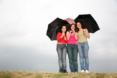Three women with umbrellas royalty free stock images