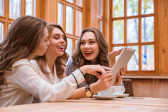 Three women using tablet computer in cafe Stock Image