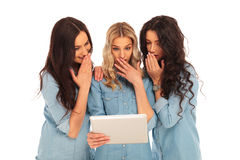Three women using a tablet pad computer are shocked Royalty Free Stock Photo