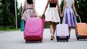 Three women walk suitcases, shopping bags arrive to rest on vacation, back view. stock video footage