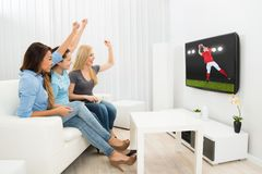 Three women watching rugby match Stock Images