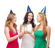 Three women wearing hats with champagne glasses Stock Photo