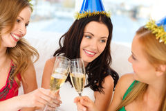 Three women wearing hats with champagne glasses Royalty Free Stock Photo