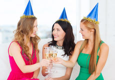 Three women wearing hats with champagne glasses Royalty Free Stock Photography